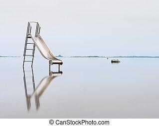 Old steel slide in lake. Chrome ladder tower with  sliding track, big granite stones around.