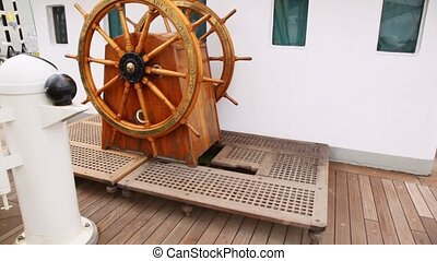 Old steering wheel from wood stands on sailing vessel deck...