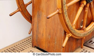 Old steering wheel from wood stands on sailing vessel deck....