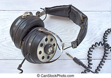 Old stereo headphones on white wooden background