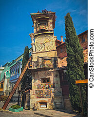 Old stone ancient carved beautiful antique European clock tower with dial on the background of the blue sky and the tourist city. European old architecture