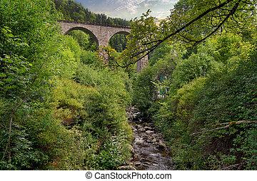 stone arch train trestle over creek