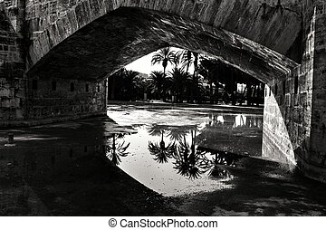 Stone bridge and reflections in a park puddle