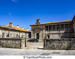 Old stone building with walled fence and cobblestone alley at Guarda, Portugal