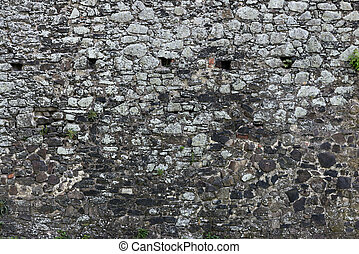 Old stone castle wall texture with cannon windows