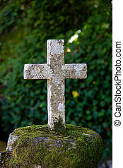 Old stone Catholic cross in the forest
