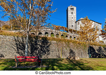 Red bench on green grass ad old stone church and belfry tower under blue sky in autumn in Locarno, Switzerland.