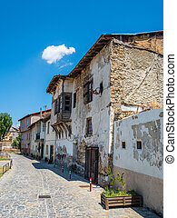 Old stone house with a wooden gate and windows on a narrow street in the city of Edessa, Greece