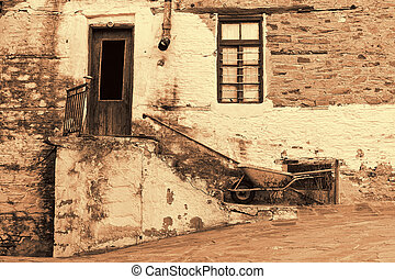 Old Stone House With Wooden Door and Window, Staircase, Rusty Gutter and Wheelbarrow in Sephia