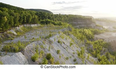 Old stone quarry open cast mine overgrown by forest, flying near cliff