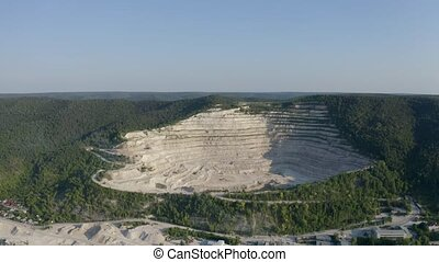 Old stone quarry opencast mine on river side in forest