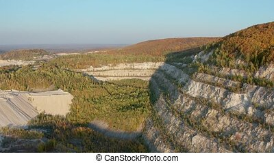 Old stone quarry opencast mine overgrown in forest