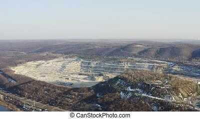 Stone quarry opencast mine with fall forest around