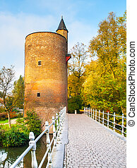 Old stone spillway tower at Minnewater lake, aka Lake of Love, in Bruges, Belgium