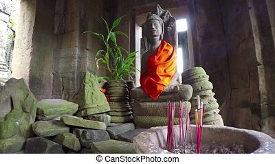 Old stone statue of Buddha among the ruins of Bayon temple