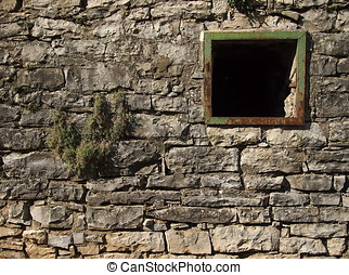 Old stone wall with a broken window