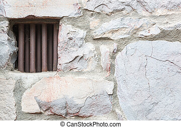 Old Stone Wall With Small Iron Barred Prison Cell Window