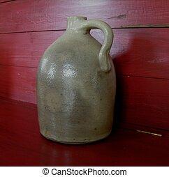 Old Stoneware Jug. - Old Stoneware Jug on red shelf.