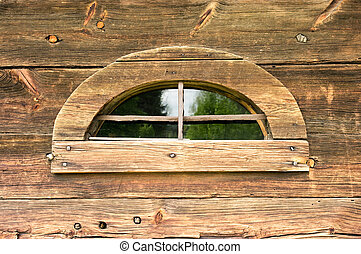 Old strange window in wooden wall