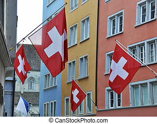 Old street in Zurich decorated with flags for the Swiss National Day, 1st of Augus