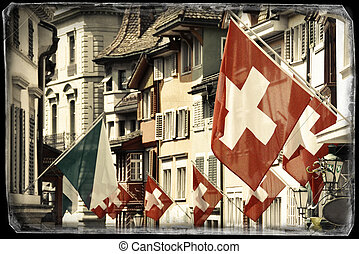 Old street in Zurich decorated with flags for the Swiss National