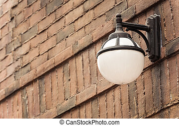 Old street lamp against a brick wall with vintage color