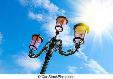 old street-lamp on blue sky with sunlight in Venice
