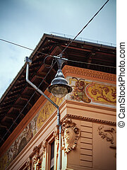 Old street lamp on crossing wires hanging above the street