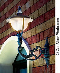 Old street lamp on the wall, glowing. Tunisia, Africa.