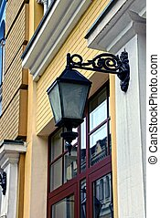 Old street lamp on the wall near the window