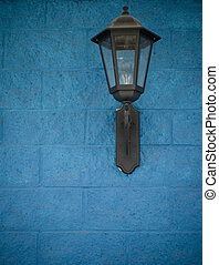 Old street light on a blue wall