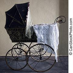 Old stroller. Antique design pram with big wheels. Historical pram.