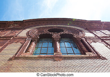 Old stucco molding window on the facade of the church with sun flare