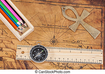 Old style brass compass and color pencil on antique map