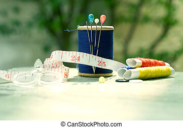 old style image of cotton reels and other sewing items on a wooden table