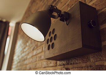 Old style lamp hanging on a brick wall