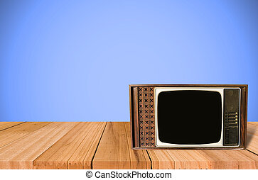 Old Style Photo. Classic vintage and retro TV on the table with blue wall background