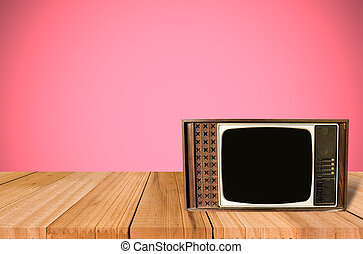 Old Style Photo. Classic vintage and retro TV on the table with pink wall background