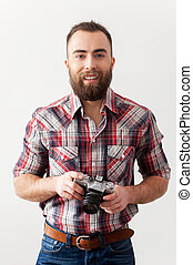 Old style photographer. Handsome young man holding a retro camera while standing against grey background