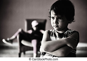 Old style photography: angry boy standing in front of relaxed girl in chair. Black and white photo, darkness, and a lot of grain added for desired effect.