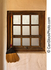 Old styled broom stick hanging by the wooden vintage window...