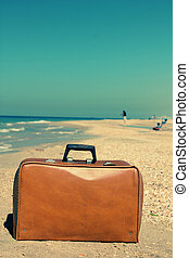 Old suitcase on the beach. Photo in old image style.