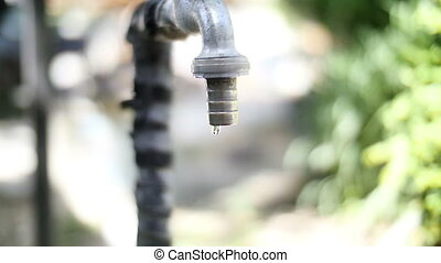 old tap closeup flowing waterdrop