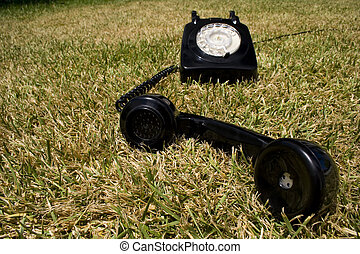 Old telephone - an old telephone on a green grass