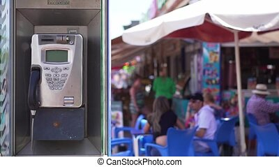 Old telephone booth on a busy street background with people...