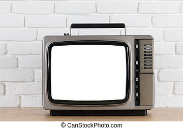 Old television with cut out screen on a white brick wall