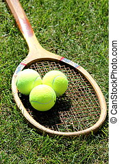 Old tennis racket on grass court
