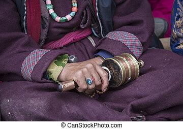 Old Tibetan woman holding buddhist prayer wheel in Lamayuru...