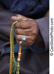 Old Tibetan woman holding buddhist rosary, Ladakh, India -...