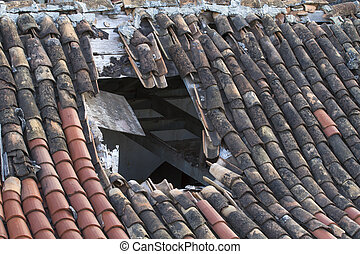 Old tiled roof with a large hole